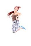 La chica joven que salta para la alegría en el fondo blanco Foto de archivo
