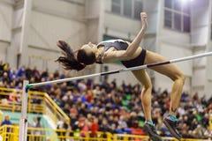 La chica joven que salta sobre barra en competencia del salto de altura imagen de archivo libre de regalías
