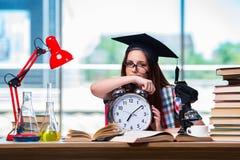 La chica joven que se prepara para los exámenes con el reloj grande Fotografía de archivo libre de regalías