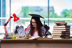 La chica joven que se prepara para los exámenes con el reloj grande Foto de archivo libre de regalías