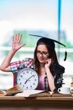 La chica joven que se prepara para los exámenes con el reloj grande Imagen de archivo