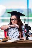 La chica joven que se prepara para los exámenes con el reloj grande Imágenes de archivo libres de regalías