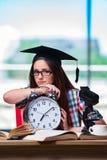La chica joven que se prepara para los exámenes con el reloj grande Fotos de archivo libres de regalías
