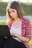 La chica joven que se sienta al aire libre en hierba trata en el ordenador portátil, funcionamiento, mirada pensativa, un día de  Imagen de archivo