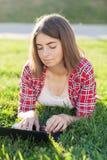 La chica joven que se sienta al aire libre en hierba trata en el ordenador portátil, funcionamiento, mirada pensativa, un día de  Imágenes de archivo libres de regalías