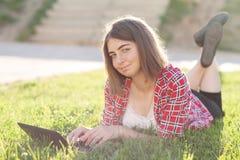 La chica joven que se sienta al aire libre en hierba trata en el ordenador portátil, funcionamiento, mirada pensativa, un día de  Imagenes de archivo