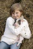 La chica joven que se sienta en el heno, sonriendo y sosteniendo un cerdo en el suyo sonríe Retrato de la forma de vida Imagen de archivo libre de regalías