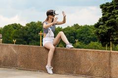 La chica joven que se sienta en las escaleras, cerca de la universidad, está en realidad virtual, en VR Foto de archivo libre de regalías