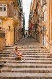 La chica joven que se sienta en las escaleras traga las calles estrechas de La Valeta foto de archivo