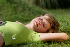 La chica joven que tiene un resto en una hierba Fotos de archivo libres de regalías