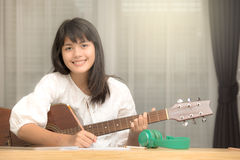La chica joven que toca la guitarra y compone música Imágenes de archivo libres de regalías