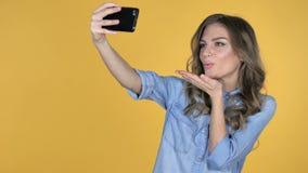 La chica joven que tomaba Selfie con Smartphone aisló en fondo amarillo metrajes