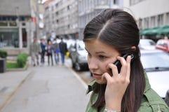 La chica joven realiza una llamada a un teléfono móvil Foto de archivo libre de regalías