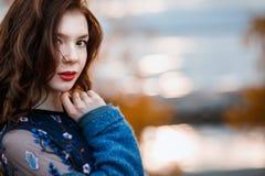 La chica joven rizada hermosa del retrato del primer que mira a la cámara que lleva la capa azul y el vestido en otoño parquean Imagenes de archivo