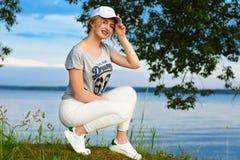 La chica joven romántica en deportes viste con un casquillo en la luz del sol contra el contexto de la orilla del agua del lago e Imagen de archivo