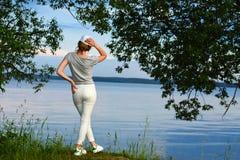 La chica joven romántica en deportes viste de la parte posterior en la luz del sol contra el contexto de la orilla del agua del l Fotografía de archivo