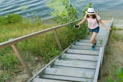 La chica joven romántica en sombrero se alza la escalera de madera Río del fondo, naturaleza, verano foto de archivo