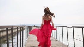La chica joven romántica en vestido rojo está corriendo sobre el embarcadero de madera viejo del mar, visión trasera metrajes