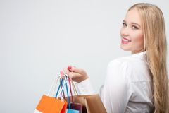 La chica joven rubia alegre está haciendo compras Imagenes de archivo