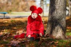 La chica joven sabrosa del perno-para arriba del carro que lleva la chaqueta ruborosa roja del invierno y el sombrero caliente co Fotos de archivo