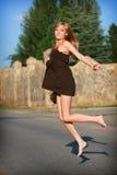 La chica joven salta en el camino Fotografía de archivo libre de regalías