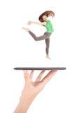 La chica joven salta usando la PC de la tableta en la mano de la gente Imagenes de archivo