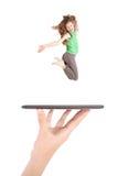 La chica joven salta usando la PC de la tableta en la mano de la gente Foto de archivo libre de regalías