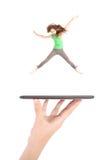 La chica joven salta usando la PC de la tableta en la mano de la gente Foto de archivo