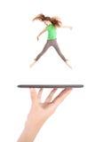 La chica joven salta usando la PC de la tableta en la mano de la gente Imagen de archivo libre de regalías