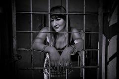 La chica joven se cerró detrás de las barras, rejilla, como en la prisión el parecer atractivo en falda corta Imágenes de archivo libres de regalías