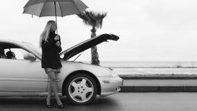 La chica joven se coloca al lado de un coche quebrado bajo ayuda que espera del paraguas para metrajes