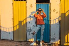 La chica joven se coloca cerca de una pared colorida y mira a través de los prismáticos Imágenes de archivo libres de regalías