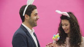 La chica joven se coloca en un fondo rosado Ella se acerca a un hombre y da los huevos multicolores decorativos Durante esto él