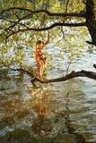 La chica joven se coloca en una rama de un árbol sobre el agua de un río y salpica su pie Foto de archivo libre de regalías