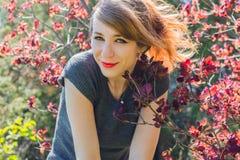 La chica joven se coloca entre brunches Imagen de archivo libre de regalías