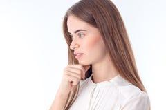 La chica joven se coloca oblicua y piensa aislado en el fondo blanco Fotos de archivo libres de regalías