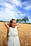La chica joven se divierte en campo de trigo Fotos de archivo