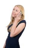 La chica joven se divierte que habla en el teléfono Foto de archivo