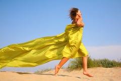 La chica joven se ejecuta en la arena en mantón amarillo de la tela Foto de archivo libre de regalías