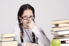 La chica joven se está sentando en su escritorio entre los libros Imagen de archivo libre de regalías
