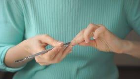La chica joven se hace la manicura con el empujador de la cutícula almacen de metraje de vídeo