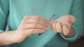 La chica joven se hace que manicure con el fichero de clavo almacen de video