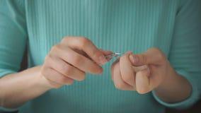 La chica joven se hace que manicure con las pinzas almacen de metraje de vídeo