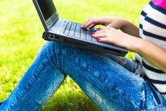 La chica joven se relaja con el ordenador portátil en parque del verano Imágenes de archivo libres de regalías