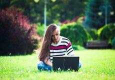 La chica joven se relaja con el ordenador portátil en parque del verano Imagenes de archivo