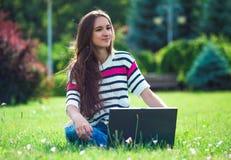 La chica joven se relaja con el ordenador portátil en parque del verano Foto de archivo libre de regalías