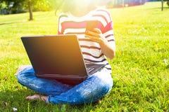 La chica joven se relaja con el ordenador portátil y el teléfono en parque del verano Imagenes de archivo