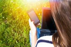 La chica joven se relaja con el ordenador portátil y el teléfono en parque del verano Imagen de archivo