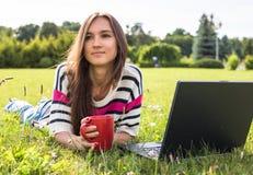 La chica joven se relaja con el ordenador portátil y la taza de café en parque del verano Imagen de archivo
