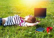 La chica joven se relaja con el ordenador portátil y la taza de café en parque del verano Foto de archivo